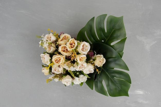 Bellissimo bouquet di rose bianche su superficie grigia.