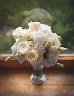 Beautiful white roses in a glass vase near window.