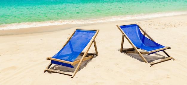 Красивый пляж с белым песком. стулья на переднем плане, рыбацкие лодки на заднем плане. пейзаж вьетнама