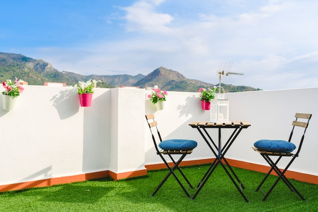 Beautiful white terrace with chairs and coffee table overlooking the mediterranean mountai