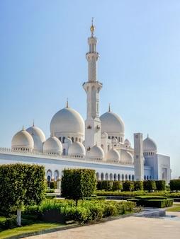 日光の空を背景にモスクの美しい白い塔。有名なシェイクザイードグランドモスク。