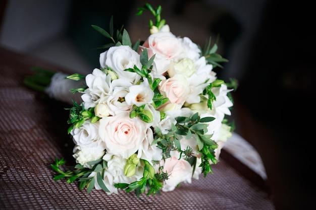 Красивый белый свадебный букет лежит на софе