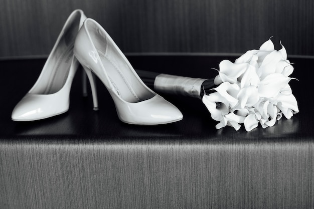 Beautiful white wedding bouquet of lilies lies next to the bride's shoes