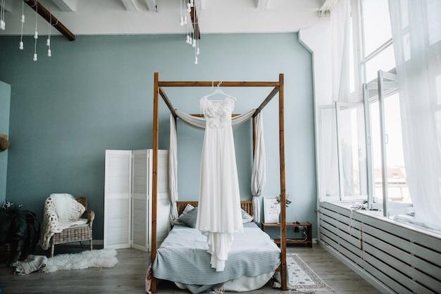 Красивое белое свадебное платье невесты перед кроватью