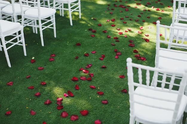 Красивые белые свадебные стулья на церемонии в парке