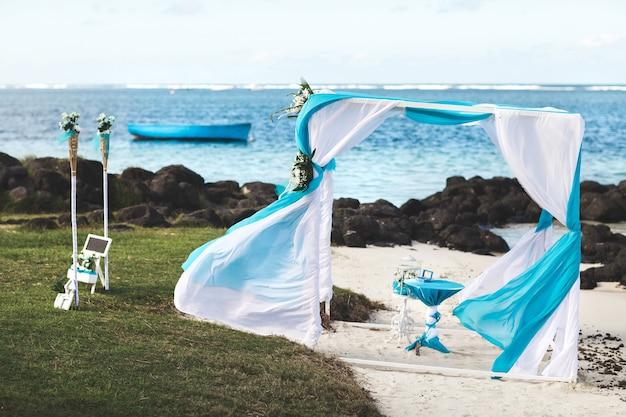 海の近くの式典のための美しい白い結婚式の装飾