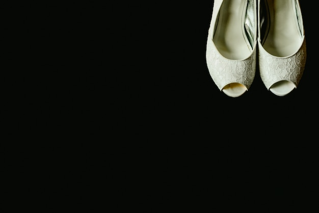 Beautiful white wedding shoes in a corner on isolated black background, copy space.