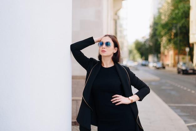 都市景観を背景に黒いドレスを着た美しい白人女性