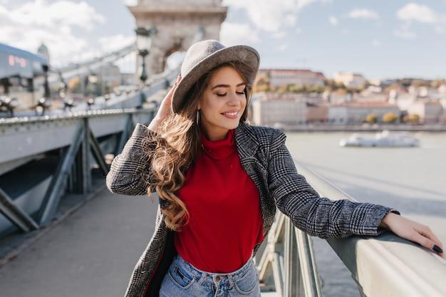 美しい白人女性は旅行で街の景色を楽しむ柔らかい赤いセーターを着ています