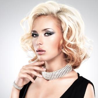 Красивая белая женщина с вьющейся прической и серебряным браслетом - позирует в студии