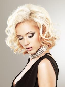 スタジオでポーズをとって巻き毛の美しい白人女性