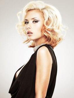 스튜디오에서 포즈 곱슬 헤어 스타일으로 아름 다운 백인 여자