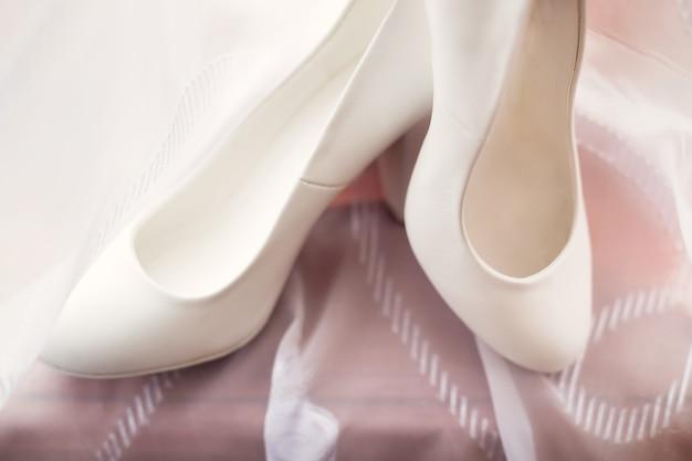Красивые белые женские свадебные туфли стоящие на тюле
