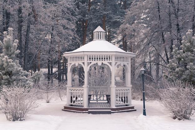 눈 덮인 나무를 배경으로 겨울 공원에 있는 아름다운 흰색 나무 전망대
