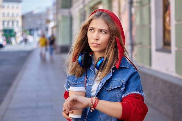 Beautiful white young woman about 25 years old in hoodie and with earphones is walking during street in saint petersburg with paper cup of coffee.