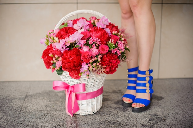 Beautiful wicker basket of flowers near the girl legs