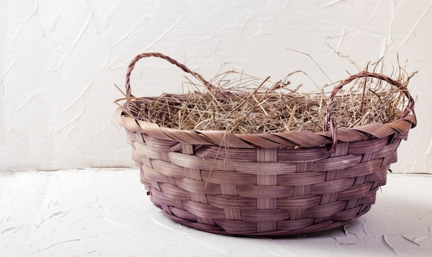 Beautiful wicker basket with hay on a white textured background.