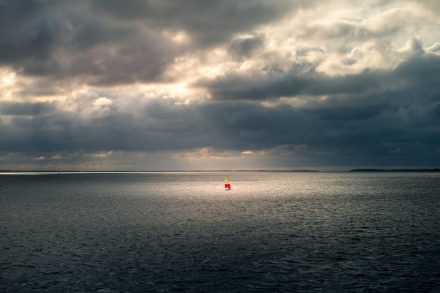 Beautiful wide dark shot of the ocean with a little red buoy visible in the distance