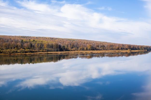Красивая, широкая осенняя река среди леса. спокойное и тихое место с осенними красками. посреди речного острова. вид сверху вдаль