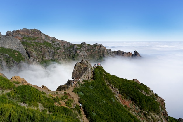 Beautiful wide shot of green mountains and white foggy clouds