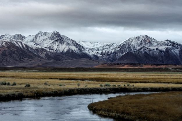 Beautiful wide shot of mountains surrounded by a river and flat grass fields