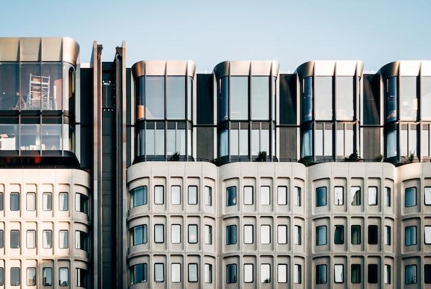 澄んだ青い空の下で大きなガラス窓のあるモダンな白い建築の美しいワイドショット