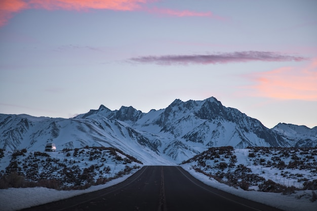 Beautiful wide shot of a road near mountains filled with snow under a pink and purple sky