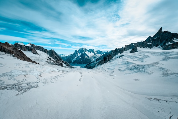 Beautiful wide shot of ruth glaciers covered in snow under a blue sky with white clouds