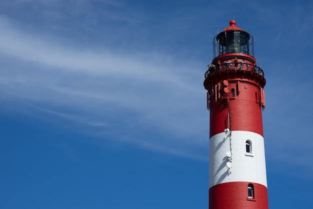 Beautiful wide shot of the top of a red and white lighthouse tower on a sunny day at the beach