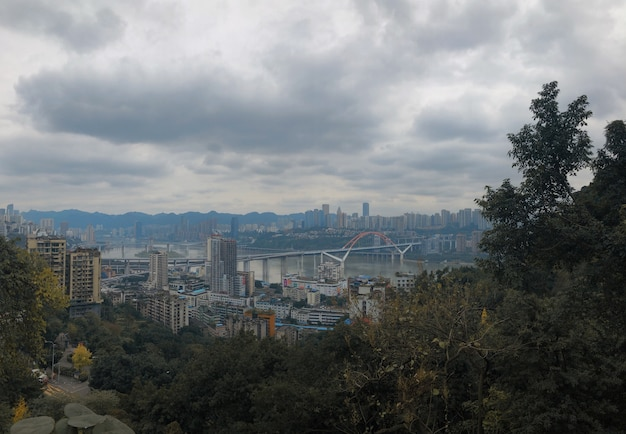 Beautiful wide shot of yuzhong qu, china with cloudy sky and greenery in the foreground