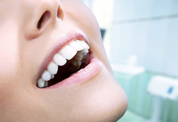 Красивая широкая улыбка молодой свежей женщины с большими здоровыми белыми зубами. изолированные на фоне
