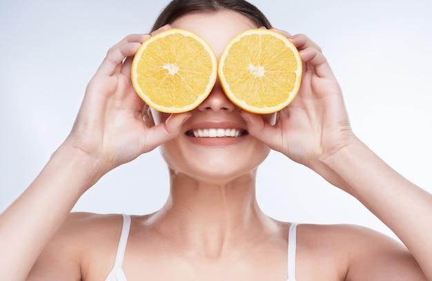 Красивая широкая улыбка, белые крепкие зубы. голова и плечи молодой женщины с белоснежной улыбкой, держащей два желтых лимона возле глаз, закрытые глаза с лимонами