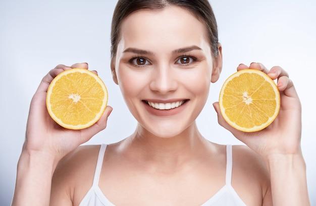Красивая широкая улыбка, белые крепкие зубы. голова и плечи молодой женщины с белоснежной улыбкой, держащей два желтых лимона возле лица, смотрящей в камеру