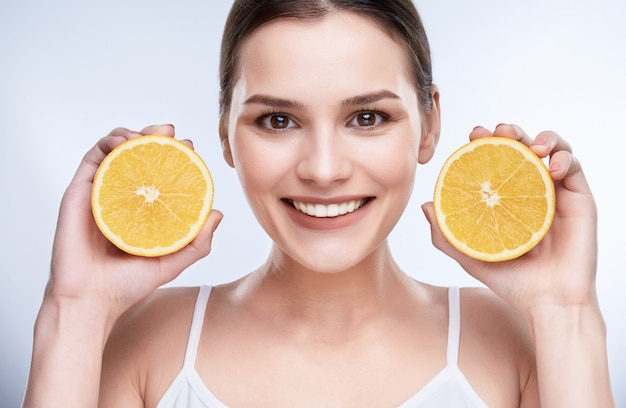 Beautiful wide smile, white strong teeth. head and shoulders of young woman with snow-white smile holding two yellow lemons near face, looking at camera