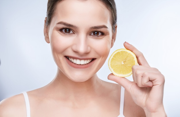 Beautiful wide smile, white strong teeth. head and shoulders of young woman with snow-white smile holding yellow lemon, looking at camera