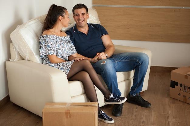 新しいアパートのソファで休んでいる美しい妻と夫。かわいい瞬間を持っている幸せなカップル