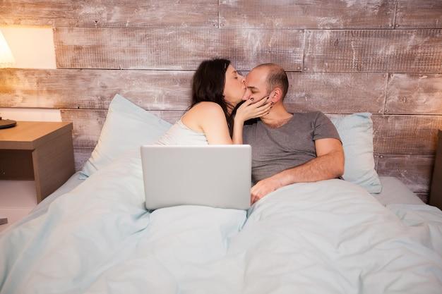 就寝前に美しい夫にキスをするパジャマ姿の美しい妻。ベッドの上のラップトップ。