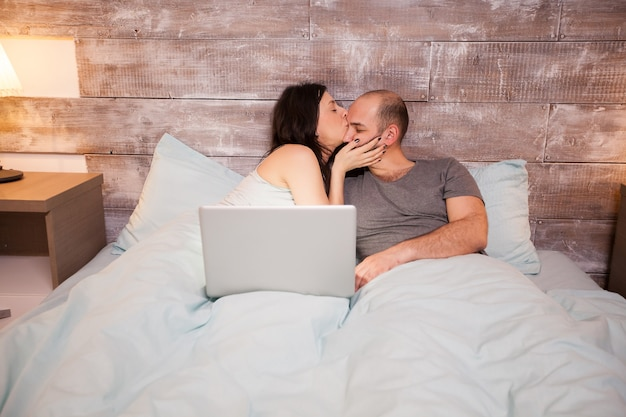 Beautiful wife in pajamas kissing her beautiful husband before bedtime. laptop on bed.