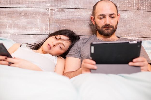 Bella moglie in pigiama che dorme mentre suo marito sta lavorando al computer tablet.