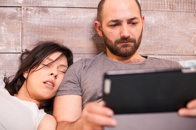 Beautiful wife sleeping on her husband husband while he is working late on tablet computer.