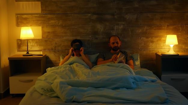 잠자기 전에 전화 앱에서 방 조명을 켜고 있는 아름다운 아내. 책을 읽는 남편.