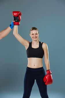 Beautiful winner. blond hair woman in red boxing gloves standing on gray background