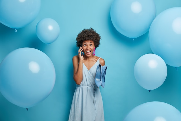 Beautiful winsome joyous woman organizes and prepares party event, invites friends via smart phone, chooses outfit to look brilliant, dressed in long dress and holds blue shoes, celebrates birthday