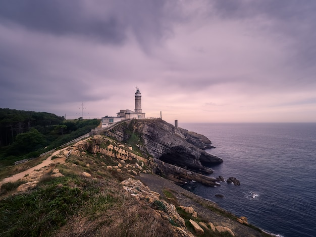 Beautiful winter cloudy sunset, on cliff and lighthouse, of santander, spain