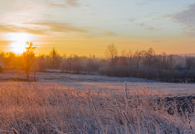 Beautiful winter frozen rural landscape at sunset
