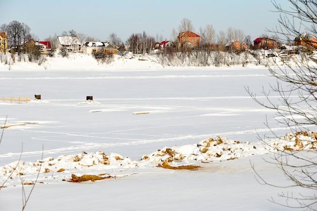 아름다운 겨울 풍경-컨트리 하우스, 강, 나무가 하얀 눈으로 덮여 있습니다.