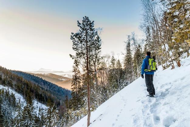 Красивый зимний пейзаж в горах и молодой человек-путешественник, наслаждаясь видом на горы