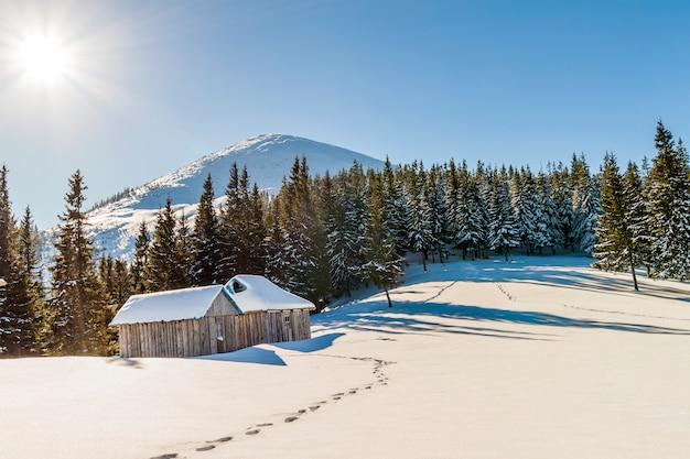 草原と小さな小さな家の雪道と山の美しい冬の風景。幸せな新年のお祝いのコンセプト。