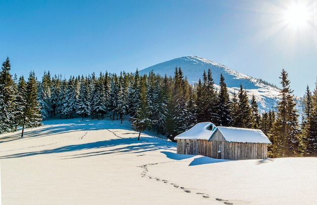 草原と小さな小さな家の雪道と山の美しい冬の風景