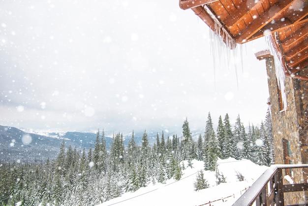 つららのあるシャレーのポーチから撮影された背の高いモミの木と山々の美しい冬の風景。ウィンタースポーツとレジャーのコンセプト。コピースペース